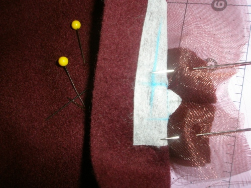 sew lips of button hole to triangles of buttonhole opening. start with sewing the two sides, then sew the top and bottom, keeping the center folds centered and straight.